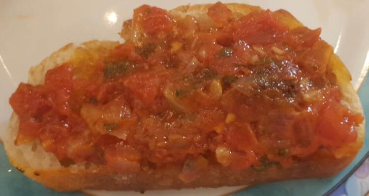 Pan con tomate mit Tomaten darauf
